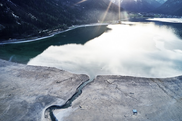 Красивый снимок озера с отражением неба и трещины на берегу