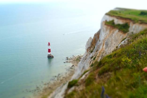 崖の近くの穏やかな海の灯台の美しいショット