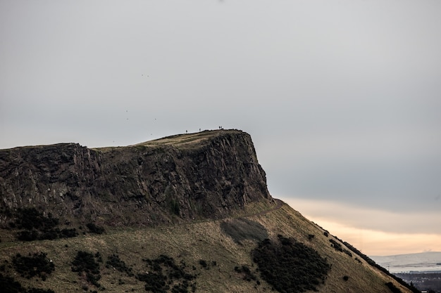 Красивый снимок людей, стоящих на вершине утеса вдалеке
