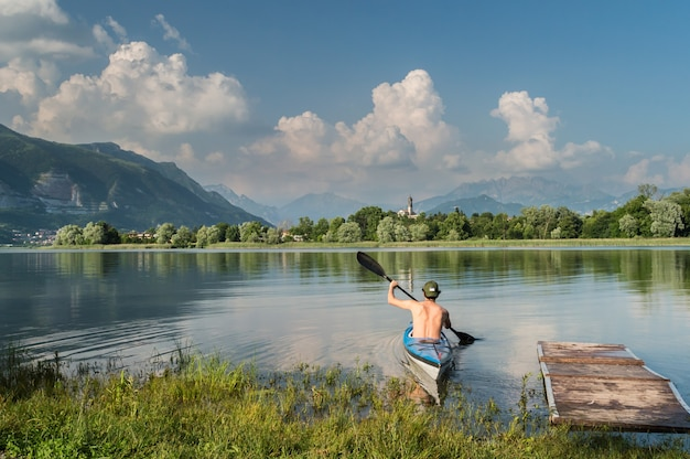 木々や山々に囲まれた湖でボートを漕ぐ人の美しいショット