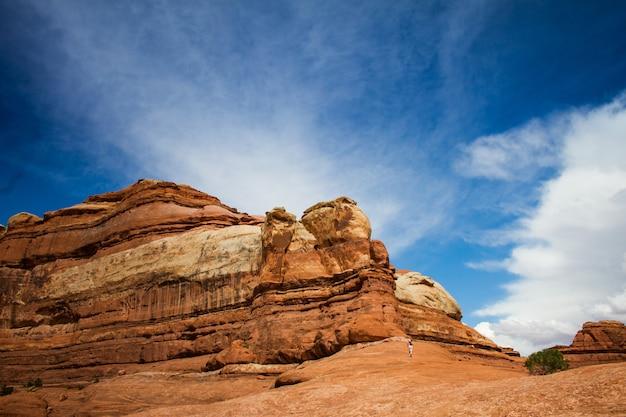 Красивый снимок человека, бегущего к пустынному утесу под облачным небом