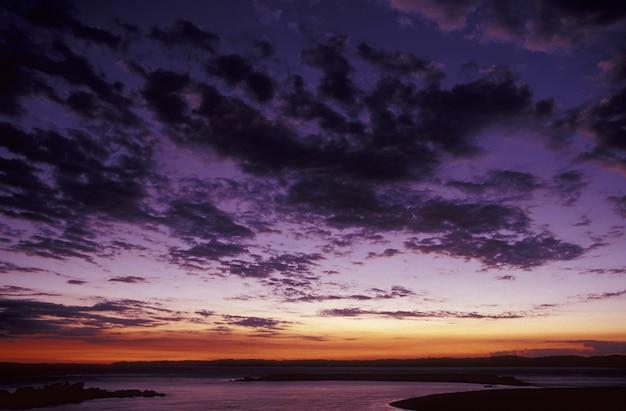 Красивая съемка фиолетового неба с облаками над морем на закате