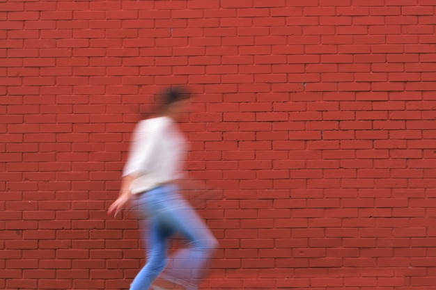 붉은 돌 벽의 아름 다운 샷과 캐주얼 의류에 여자의 개요