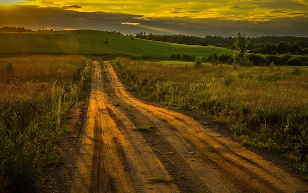 見事な夕日の中でフィールドを通る道路の美しいショット