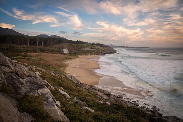 曇った青い空に沈む夕日の風景と海岸の美しいショット