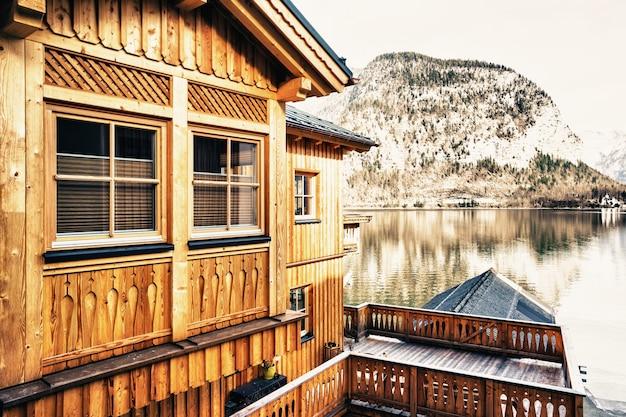Красивый снимок небольшой деревни, окруженной озером и заснеженными холмами.