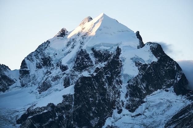 낮에 맑은 하늘과 눈 덮인 산의 아름다운 샷