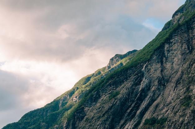 Красивый снимок крутой скалы с зеленью на нем в горах в пасмурный день