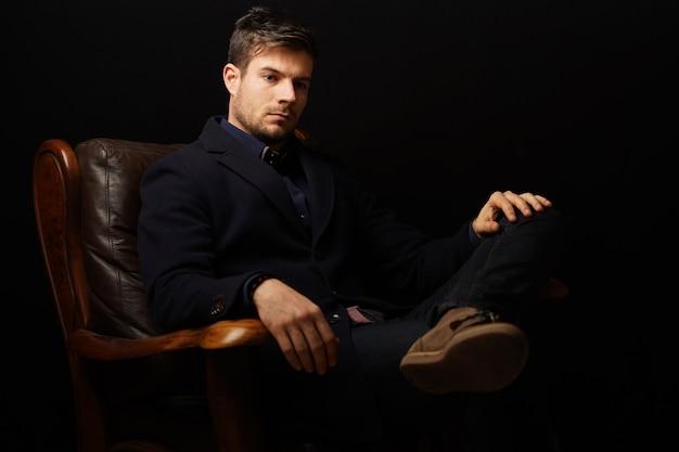 革のソファに座って考えている成功した実業家の美しいショット