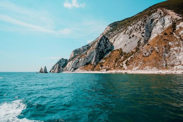 맑은 날에 맑은 물에 둘러싸인 열대 섬의 아름다운 샷