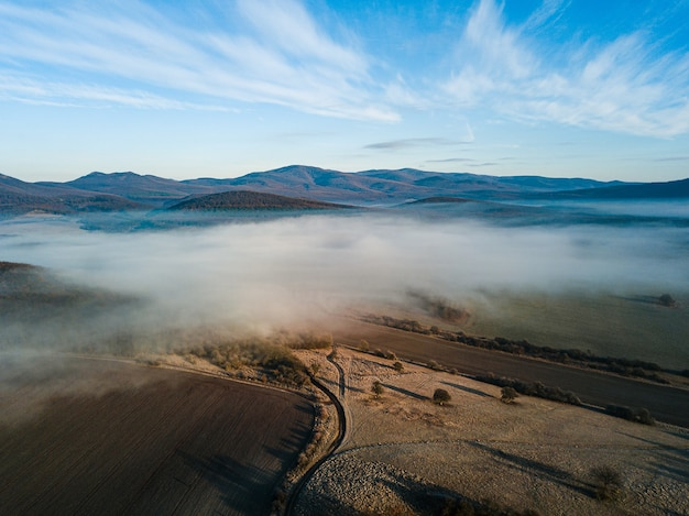 Красивый снимок белого тумана над полем с дорогой и горами с голубым небом