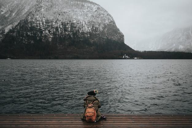 冬の霧の日の水の前に木製のドックに座っている女性の美しいショット