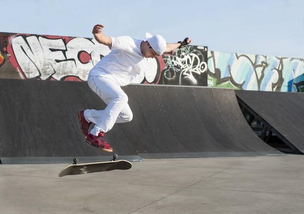 스케이트 보드 묘기를하는 젊은 백인 남성의 아름다운 샷