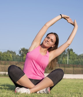 フィールドで実行する前に体を伸ばしている若い女性の美しいショット