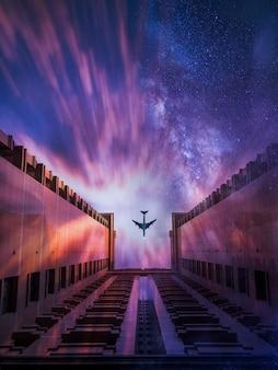 백그라운드에서 별이 빛나는 하늘로 건물을 지나가는 비행기의 아름다운 샷