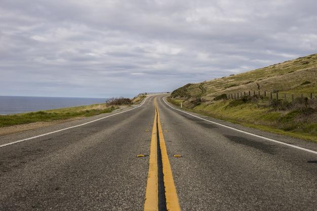 Красивый снимок асфальтовой дороги в окружении гор и океана в пасмурный день