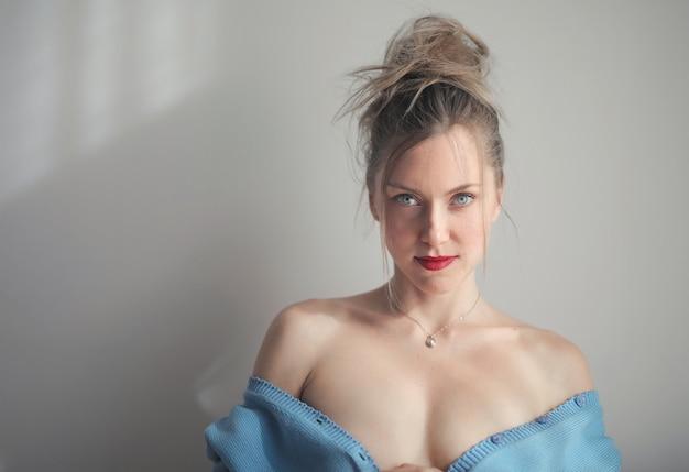 벽에 기대어 빨간 립스틱을 입고 매력적인 여성의 아름다운 샷