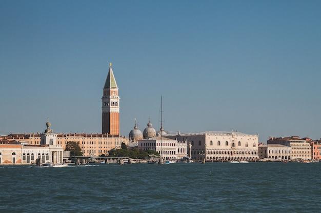 イタリアのヴェネツィアの運河の距離にある建物の美しいショット
