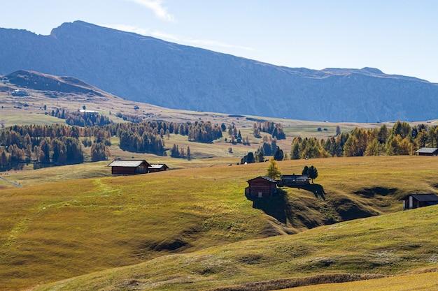 ドロマイトイタリアの草が茂った丘の上の建物の美しいショット