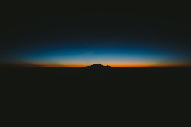 Красивый снимок темных холмов с изумительным оранжевым и синим закатом на горизонте