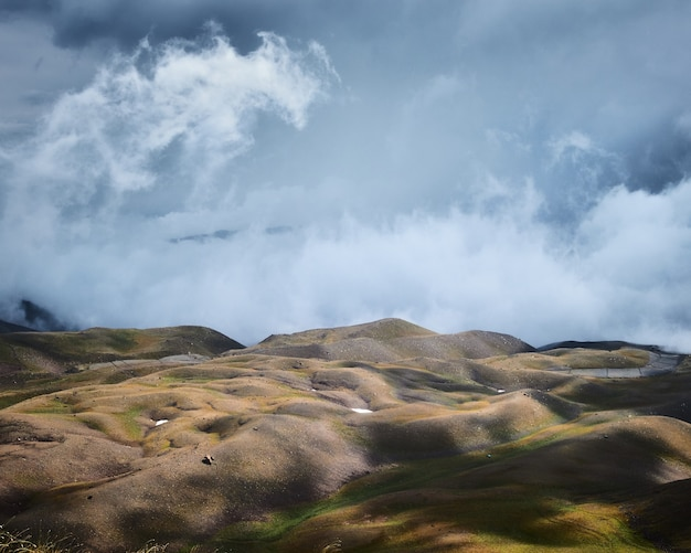 Красивый снимок пустых травянистых холмов под голубым облачным небом