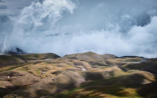 背景に青い曇り空のある丘の美しいショット