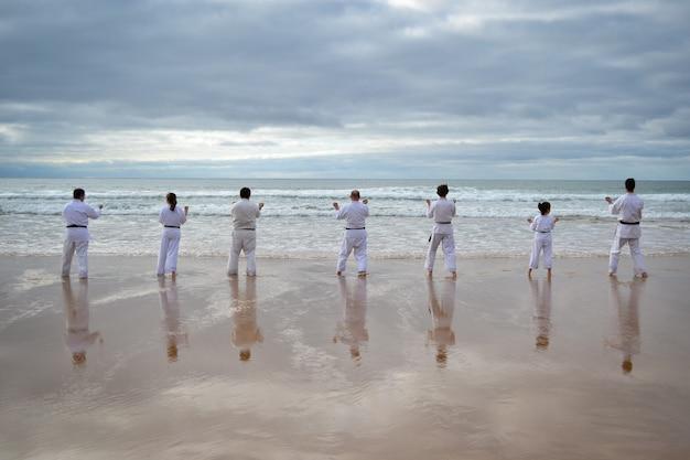 Красивый снимок игроков карате, тренирующихся на берегу моря