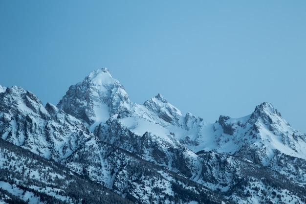 Красивый снимок гор, покрытых снегом под ясным голубым небом
