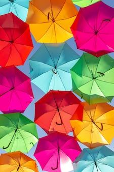 青い空を背景に色とりどりの浮かぶ傘の美しいショット