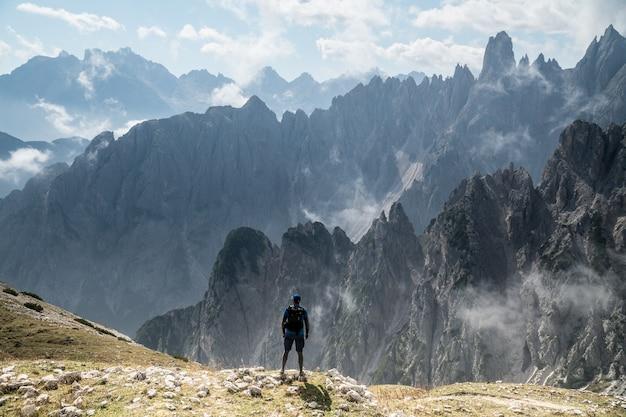 Красивый снимок человека, стоящего на скале, смотрящего на природный парк «три пика» в тоблахе, италия