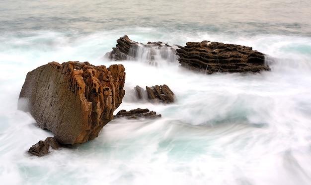 물결 모양의 바다에있는 바위의 아름다운 샷