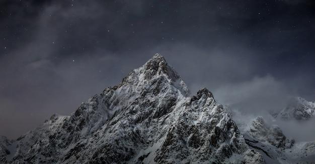 Красивый снимок скалистых гор, покрытых белым снегом