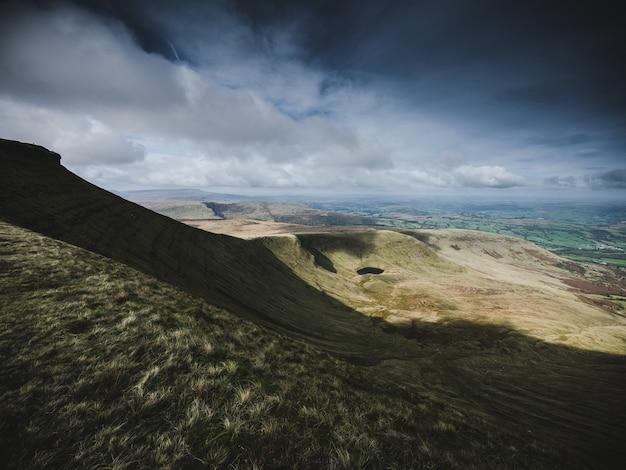 息をのむような曇り空の下で岩が多い急な山と丘の美しいショット