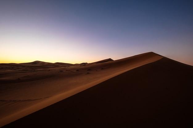 보라색과 푸른 하늘 아래 모래 언덕의 아름다운 샷