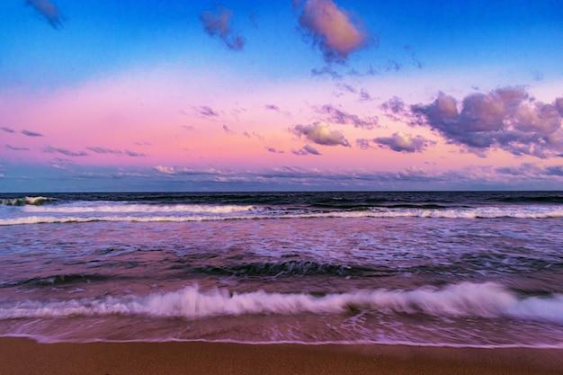 曇り空を背景にビーチに沈む夕日の風景の美しいショット