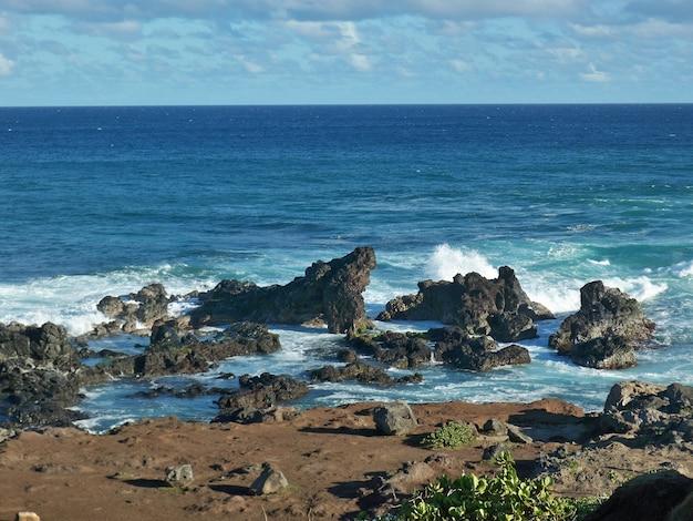 ハワイの岩に水しぶき海の波の美しいショット