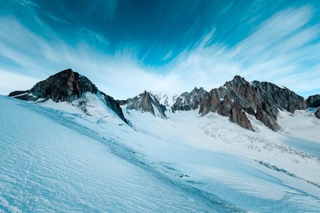 어두운 푸른 하늘이 눈 덮인 산의 아름다운 샷