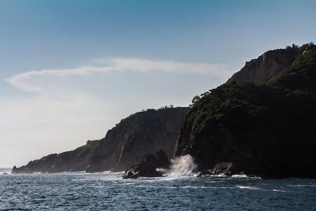 Красивый снимок сильных морских волн, падающих на скалу с голубым небом