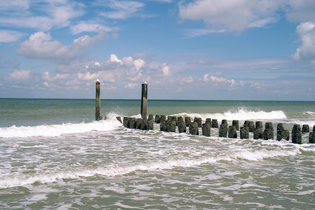 波状の海につながる上に苔が付いた背の高い石と短い石の美しいショット