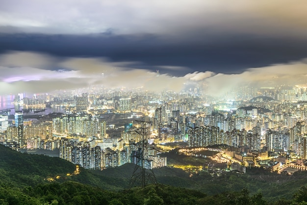 Красивый снимок высоких городских зданий под облачным небом ночью
