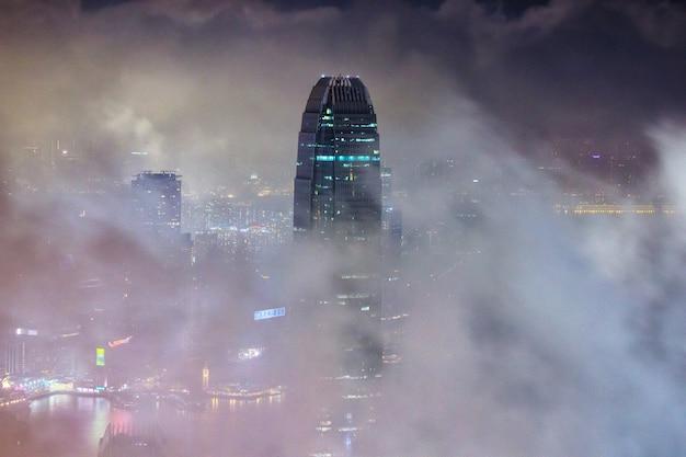 夜の曇り空の下で背の高い都市の建物の美しいショット