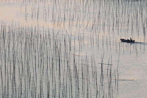 Красивый снимок рыбацкой лодки в океане во время заката в ся пу, китай