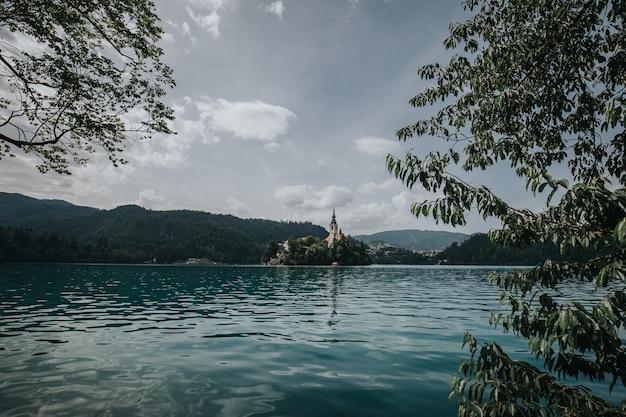 Красивый снимок озера кровоточил со зданием в окружении деревьев на расстоянии