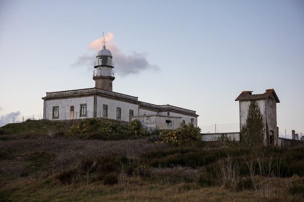 Красивый снимок маяка ларино на холме в галисии, испания, во время заката