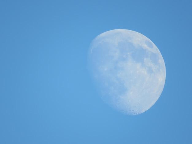 澄んだ青い空の月の美しいショット