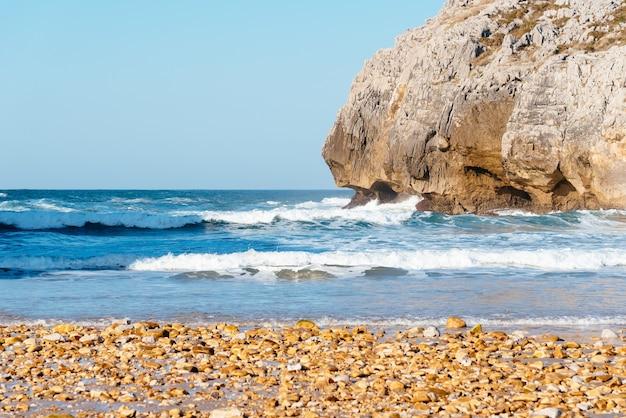Красивый снимок океанских волн, разбивающихся о скалы возле пляжа
