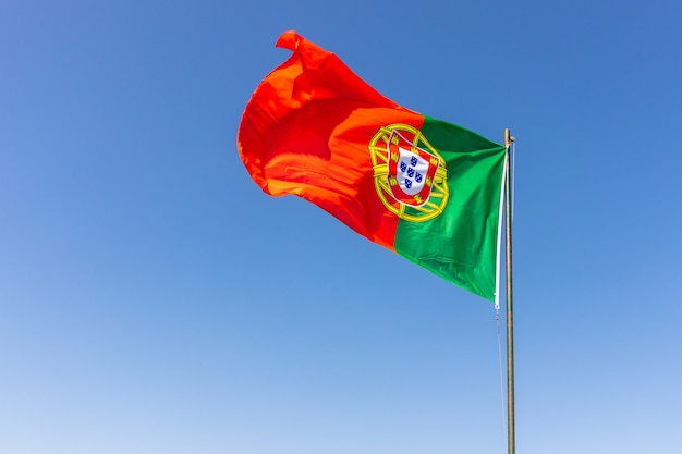 진정 밝은 하늘을 흔들며 포르투갈 국기의 아름다운 샷