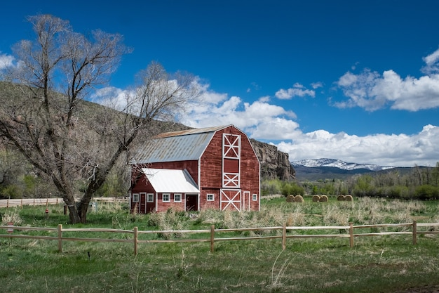 Красивый снимок красного деревянного скотного двора в поле