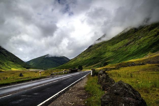 曇り空の下で山々に囲まれた道路の美しいショット