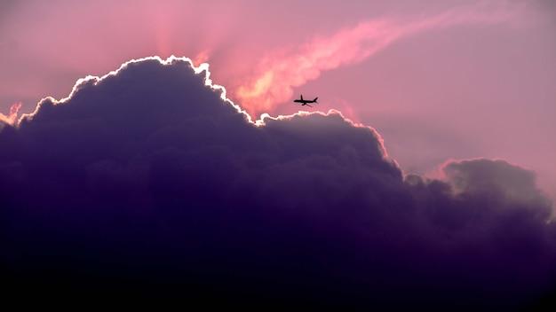 日の出の間に空を飛んでいる飛行機のシルエットの美しいショット